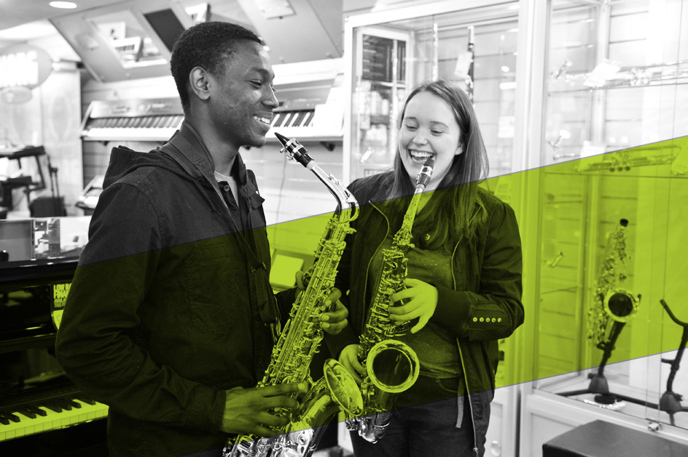 Two young people playing saxophones in a music shop