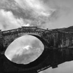 Black and white image of a bridge over water and the still reflection in the water